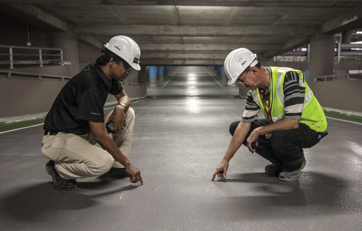 Workers inspecting a newly laid floor